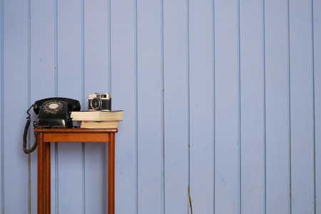 Old phone, books and camera on stool table with blue pastel wooden wall