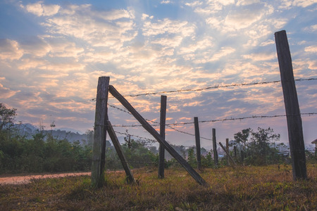 Barb wire wooden fence in the country side with stunning morning sky