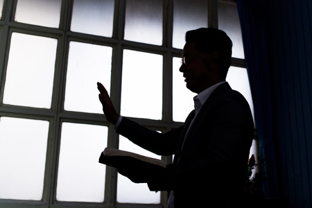 Silhouette of pastor wearing suit with rectangular window frame