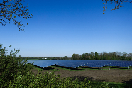 Solar cell farm in  field with blue bright clear sky