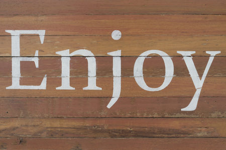 White paint word ENJOY on wooden wall