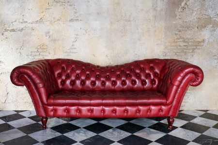 Red leather sofa in grungy room with black and white marble tile floor 스톡 콘텐츠