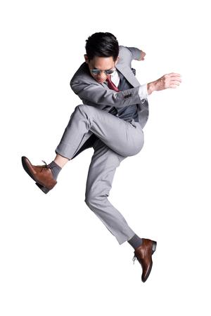 Hombre de negocios asiático joven en pose de patada saltando traje. Estudio fotográfico