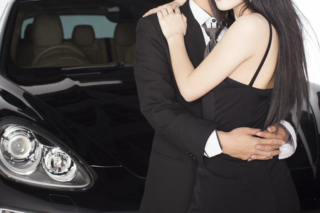 Couple hugging holding each other in front of black luxurious car Stockfoto