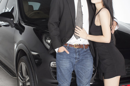 Couple hugging holding each other in front of black luxurious car 版權商用圖片