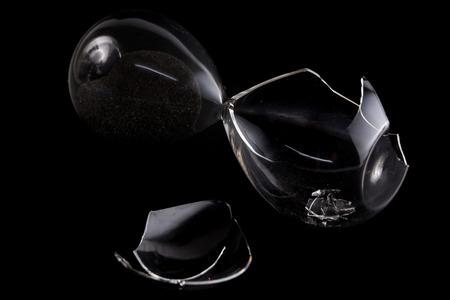 Broken hour sand glass on black background, bad time management concept