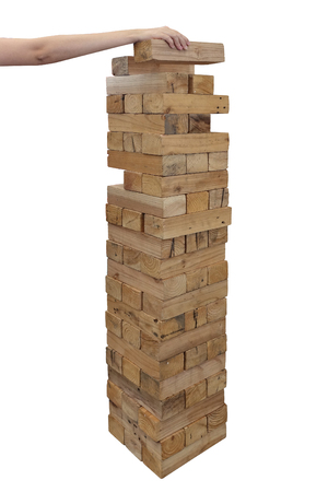 Hands playing large giant wooden tower game