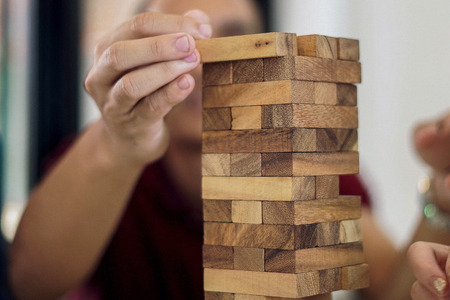 Hands playing  wooden tower game
