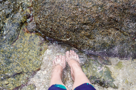 Bare feet resting on mossy rocks under shallow flowing water at the beach