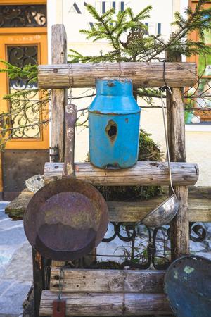 Rustic European old vintage garden decoration. Vase, pan, tree branch ladder