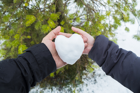 Hand holding heart shaped snow ball in winter