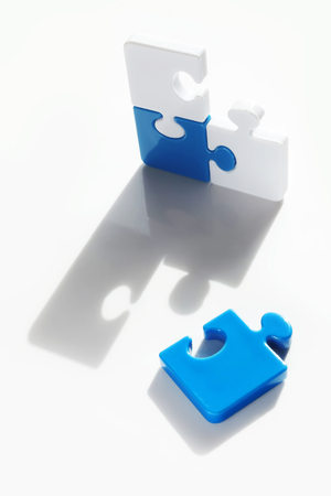 Jigsaw pieces cast shadow on white surface with one piece fall off separated from others