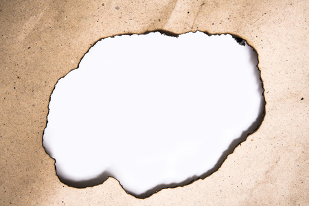 Round rough edge hole on burnt paper with white background Stock Photo