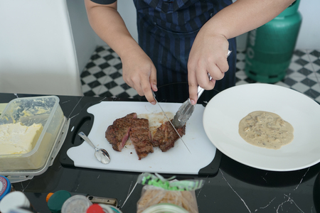 Home chef cutting meat on plastic chopping block, preparing meal at home, with gas tank blurry in the background