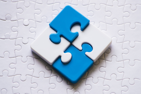 Close up blue and white plastic jigsaw. Conceptual upper and lower pieces