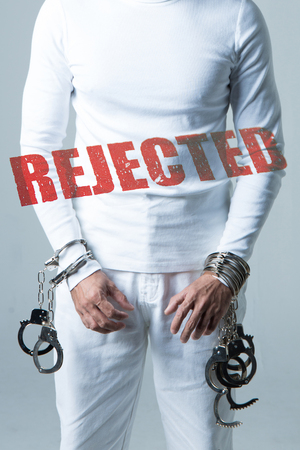 Male prisoner in white suits wearing many handcuffs, studio shot