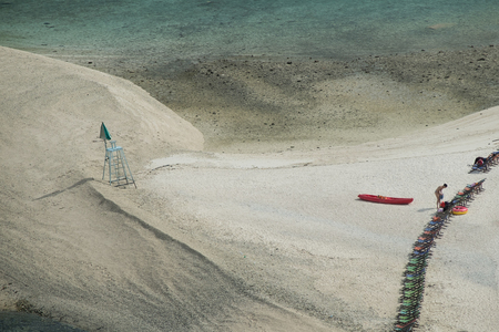 Sand beach with canoe and female tourist packing her stuff by the beach chairs