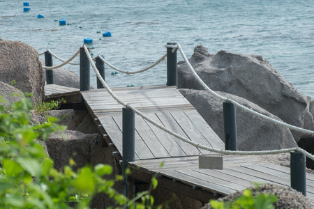 Wooden walkway along the hill with sea background