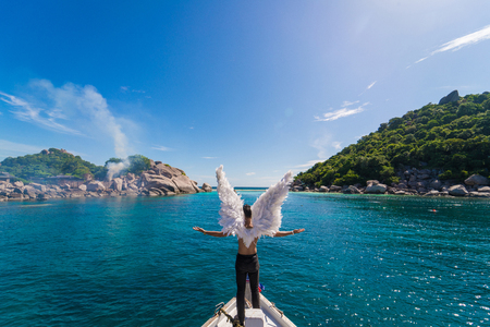 Man wearing angel wings visiting island, vacation paradise concept