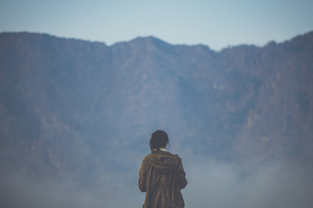 Asian tourist explore the world facing the mountain foggy hill, color filter applied