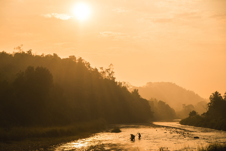 Warm toned image, silhouette of country side folks crossing river in the morning the sun ray shine through the hills