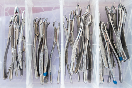 Many dental forceps in plastic container