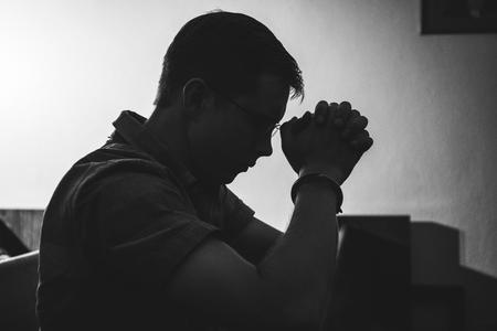 Silhouette of man praying in church in monotone