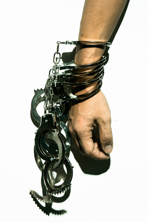 Harsh lighting image of hand being cuffed by many handcuffs, conceptual image of someone who keeps doing crimes