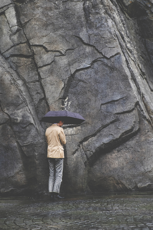 Man under umbrellar wearing casual suit facing dead end stone wall in the rain. Conceptual image of facing life crisis problem