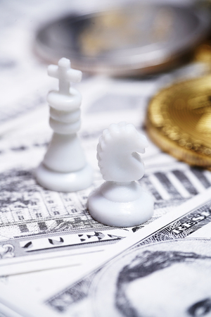 Chess pieces with bitcoins on US dollars background, conceptual photography, money game