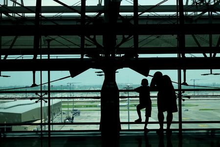 Silhouette of father and son at the airport terminal sending off someone Stok Fotoğraf - 119845715