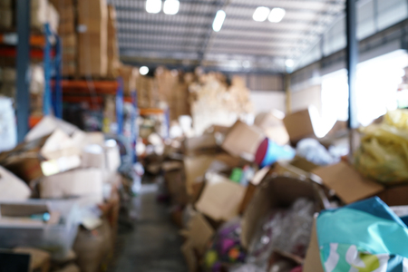 Blurry image of poorly organized warehouse with a lot of messy stocks and boxes 免版税图像