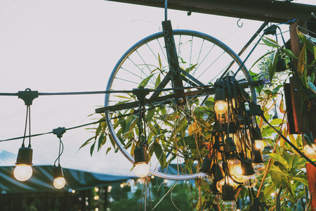 Vintage minimal light bulbs hanging with garden decorative wheel, color filter applied for soft vintage look