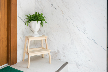 White classic vase for plant on clean wooden stair step stool in front of the house with door and welcome mat