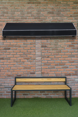 awning on brick wall with wooden bench and artificial grass