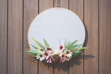 Wooden embroidery hoop with white plain fabric and flower decoration hanging on wooden pattern wall