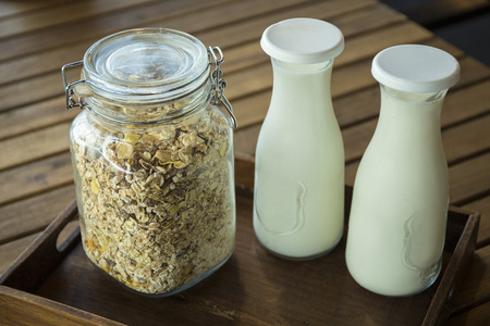 Cereal and milk in classic retro containers on wooden platter. Served in the morning for good health 免版税图像