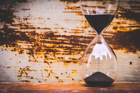 Glass hour, black sand dropping with rusty background Standard-Bild - 119841230