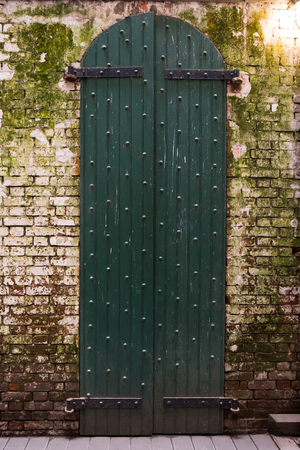 Tall vintage old gate and grungy old white brick wall