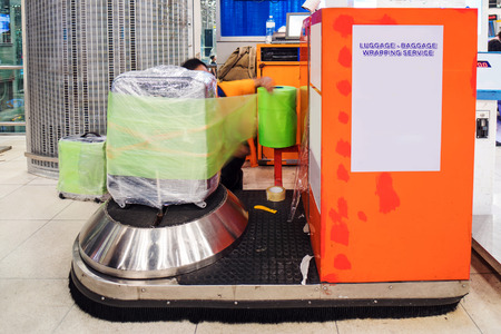 Luggage wrap machine service at the airport Stock Photo