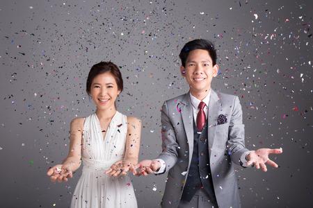 Koppel gooit glinsterend papier om hun huwelijk te vieren