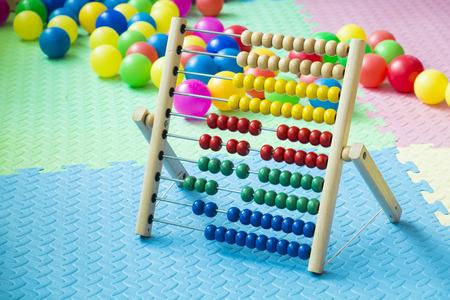 Ábaco de colores para niños en la sala de juegos con bolas de plástico y suelo de espuma suave