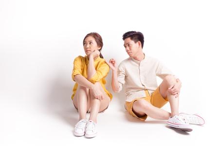 Młoda nadąsana azjatycka kobieta i młody mężczyzna próbuje się pogodzić. siedzi na białym tle