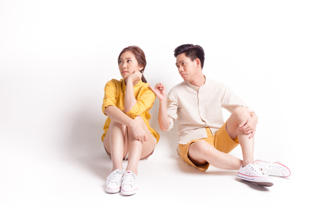 Young sulky asian female and young man trying to reconcile. sitting on white background