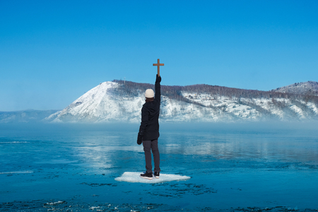 Man standing on ice floes floating in river in winter holding wooden cross with background of snow mountain