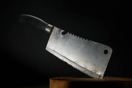 Old cleaver stuck on wooden cutting board with dark background Stok Fotoğraf