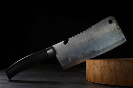 Old bent cleaver stuck on wooden butcher cutting board