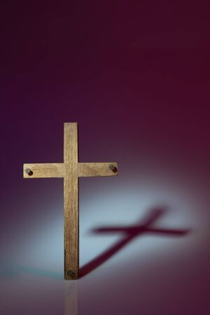 Wooden cross photographed using harsh light to make shadow cast onto the background. Shot in studio