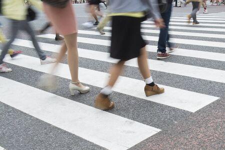 Motion blurry people walking across the zebra crossing