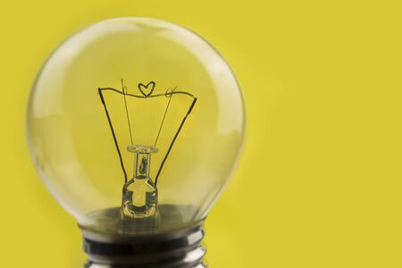 close up old obsolete light bulb with heart shaped coil Stock Photo